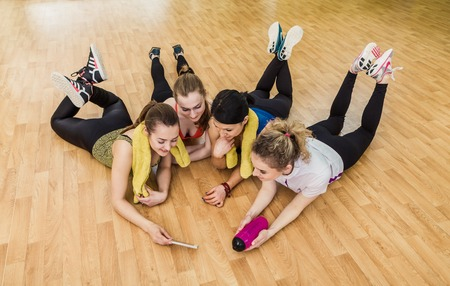 laughing girl: Group of girls in fitness class at the break looking at smartphone