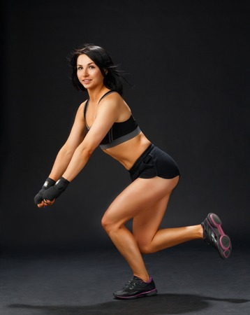 mujer sola: Mujer deportiva joven que hace �nica en cuclillas de la pierna
