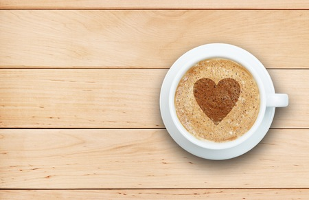 froth: Coffee concept - cup of latte with heart symbol on froth at wooden table Stock Photo