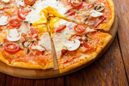 Leckere Pizza mit Champignons, Speck, Tomaten und Ei - dünne Kruste auf Holzuntergrund