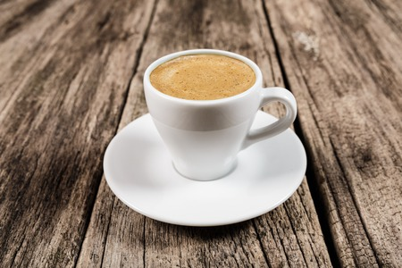crema: Coffee concept - cup of latte espresso with thick crema at wooden shabby table