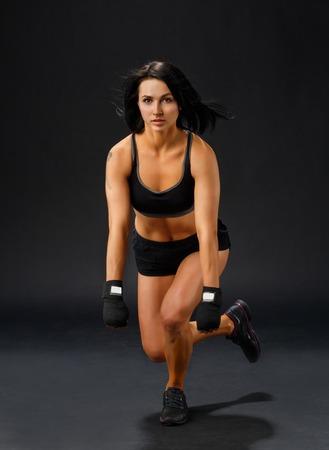 single woman: Mujer deportiva joven que hace única en cuclillas de la pierna