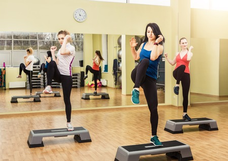 gimnasia aerobica: Grupo de mujeres jóvenes deportivas que hacen aeróbicos en la clase de gimnasia