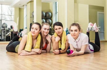 woman towel: Group of girls in fitness class at the break laying at the floor