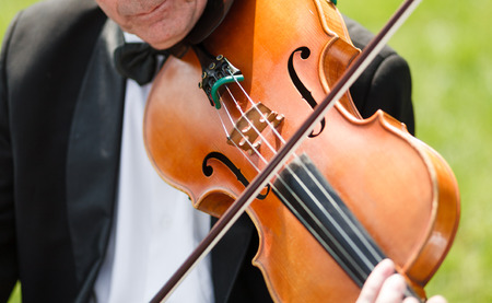 fiddle: Musician with bow tie plays violin with fiddle bow at the outdoor concert