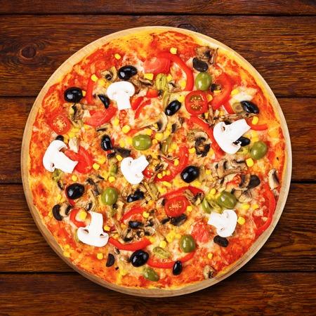 Köstliche italienische vegetarische Pizza mit Tomaten, Champignons, Paprika, Mais und schwarzen Oliven - dünne Kruste auf Holztisch Hintergrund Lizenzfreie Bilder