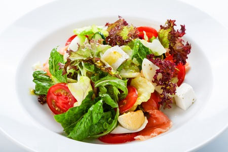 salads: Restaurant healthy food, diet nutrition - fresh salad with salmon, quail eggs, cherry tomatoes and lettuce, closeup Stock Photo