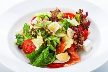 salad in plate: Restaurante comida sana, nutrici�n de la dieta - ensalada fresca con salm�n, huevos de codorniz, tomates cherry y lechuga, primer plano