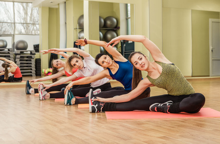 fitness woman: Group of women making stretching aerobics in the fitness class
