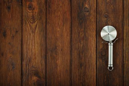 chef italiano: Acero inoxidable cortador de pizza en el fondo de madera con copyspace