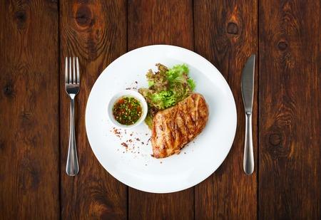 Restaurant eten - geserveerd plaat met kipfilet gegrilde biefstuk en sla op houten tafel