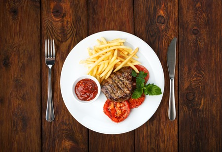 french fries plate: Restaurant food - served plate with beef grilled steak and free fries  isolated at the wooden table, above view