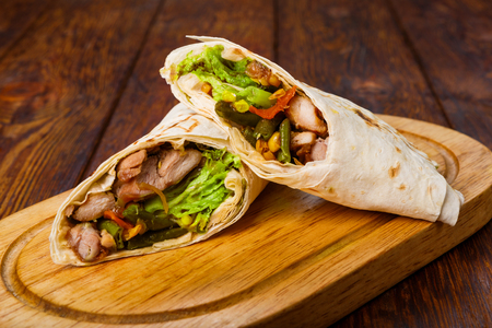 Mexican restaurant fast food - wrapped burritos with chicken and vegetables closeup at wooden desk on table