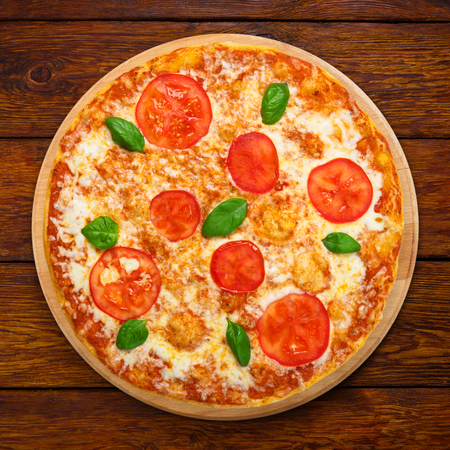 pizza: Delicious italian Margherita pizza with tomatoes and mozarella - thin pastry crust at wooden table background, above view on wooden desk