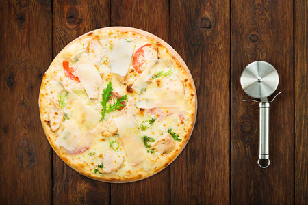 pastry cutter: Delicious pizza with chicken, parmesan, tomatoes, white sauсe and fresh arugula - thin pastry crust isolated at wooden background with stainless steel cutter, above view Stock Photo