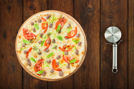 pastry cutter: Delicious seafood pizza with tuna fish, tomatoes and leek - thin pastry crust, above view isolated at wooden background with stainless steel cutter