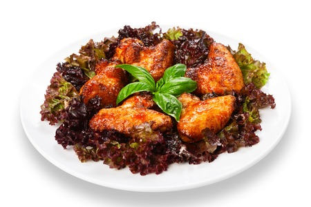 american cuisine: American cuisine, restaurant food -  fried roasted chicken wings on lettuce with basil at round white plate closeup isolated