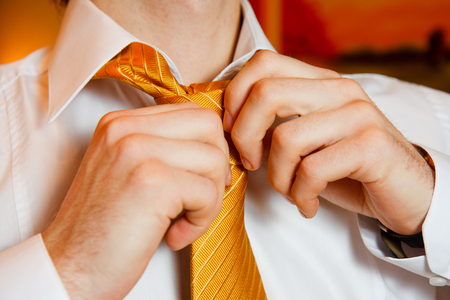 Groom morning - man's hands put yellow tie knot on