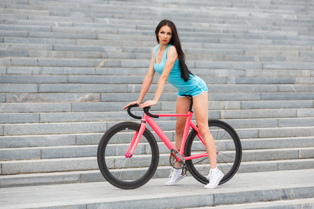 Young slim sexy sportive woman in blue shorts and white snickers long-haired, sensual posing on pink fix bicycle in urban city enviroment