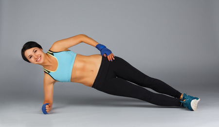 Young sportive strong brunette woman in sportswear studio shot at grey background making side plank