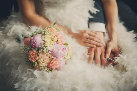 Wedding pastel bouquet closeup in front of couple - groom and bride's hands with elegant manicure. Bouquet lays on the dress with swan feather decor
