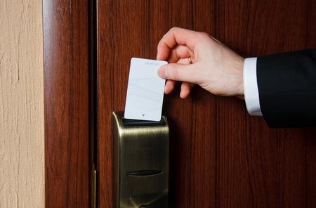 Man hand in zwart pak steekt kaart aan elektronisch slot te openen in hotel deur Stockfoto