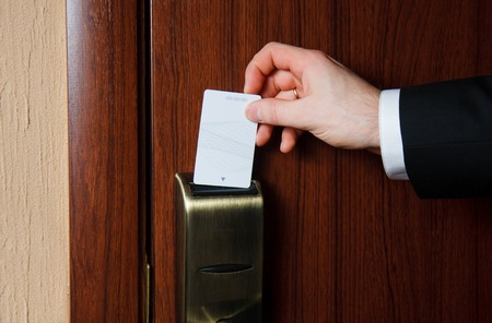 Mans hand in black suit inserts card to open electronic lock in hotel door