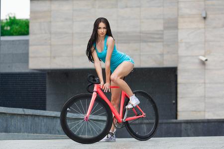 Mujer juguetona joven atractiva delgada en pantalones cortos azules y risitas blanco de pelo largo, posando sensual en la bicicleta fija de color rosa en el ambiente urbano de la ciudad Foto de archivo - 46693008
