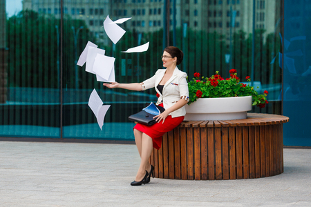 throw up: Business lady concept - young beautiful woman in suit and glasses throw up her papers in downtown. Finishing project or starting vacation Stock Photo