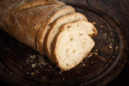 unleavened: Yeast free, no knead, unleavened  healthy organic rye wheat half sliced homemade bread loaf with sesame on a round desk at wooden table Stock Photo