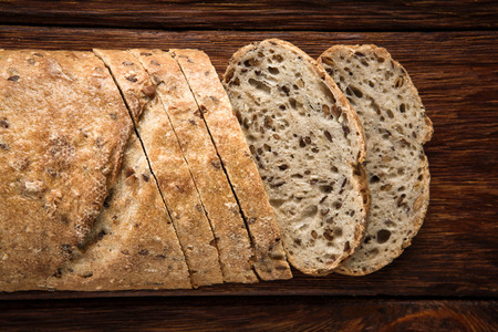 unleavened: Yeast free, no knead, unleavened  healthy organic rye wheat half sliced homemade bread loaf and pieces with sesame on a round desk at wooden table