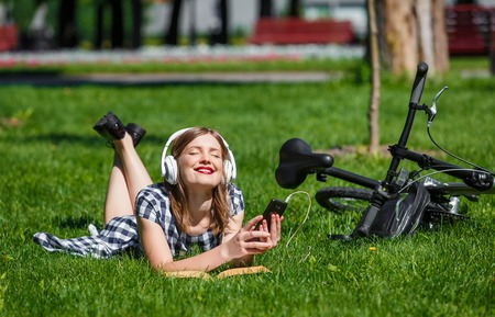 Teen student girl or young woman in plaid dress lays in the grass relaxing near a bicycle and listens music in white earphones from the smartphone in the park