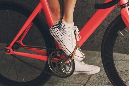 snickers: Young woman foot in white snickers shoe at pink fix bicycle pedal closeup Stock Photo