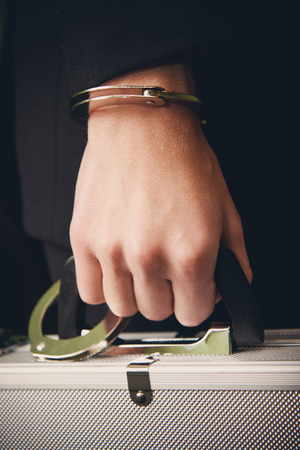hand guard: Bank finance security concept - businessman or guard hand  in handcuffs closeup holding suitcase with money