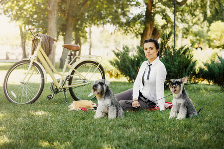british girl: Beautiful young woman in the park with vintage bicycle and two miniature schnauzer dogs having picnic in the park. Girl wears british style tweed ride