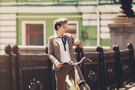 flat cap: Beautiful young woman outdoors riding vintage bicycle, looking at wrist watch. Girl wears british style tweed ride, brown plaid jacket and flat cap Stock Photo