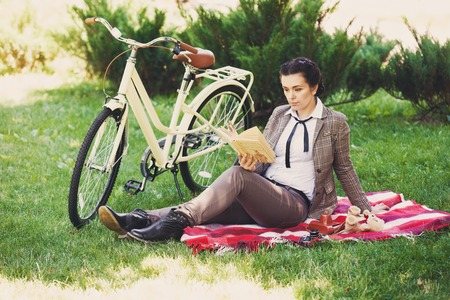 british girl: Beautiful young woman in the park with vintage bicycle reading book at the picnic in the park. Girl wears british style tweed ride