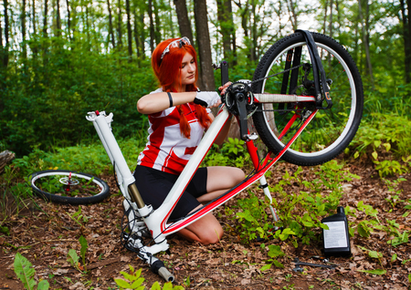 mountain bicycling: Young  sportive woman bicyclist or sportswoman bicyclist repairing her mtb bike in the forest