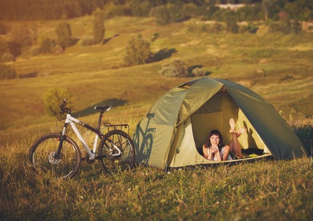road cycling: Travel with bicycle alone - young slim sportive woman tourist in the tent at the beautiful nature landscape laying in the tent Stock Photo