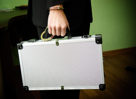 hand guard: Bank finance security concept - businessman or guard hand  in handcuffs closeup holding suitcase with money in the office