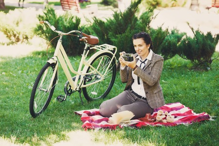 british girl: Beautiful young woman photographer in the park with vintage bicycle and old photo camera making shot at the picnic in the park. Girl wears british style tweed ride
