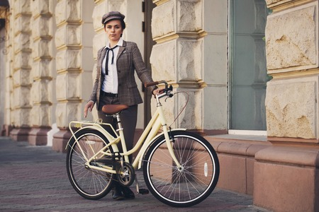 flat cap: Beautiful young woman outdoors posing vintage bicycle. Girl wears british style tweed ride, brown plaid jacket and flat cap Stock Photo