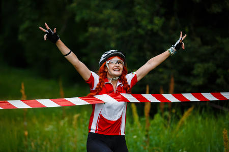 tape line: Young red-haired woman cyclist in protective helmet crossing the finish line breaking the tape - victory triumph in sportive competition, wins the cycling race