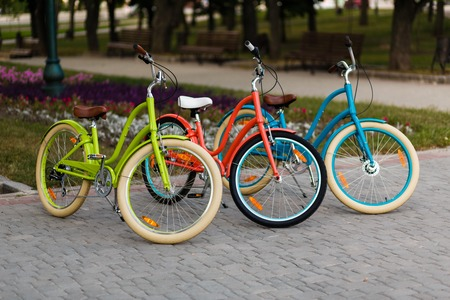 bright space: Three beautiful lady city bright colored bicycles or bikes for woman standing in the summer park outdoors