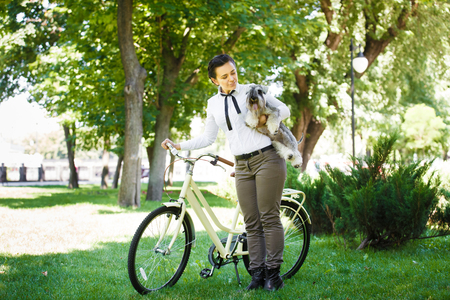 british girl: Beautiful young woman in the park with vintage bicycle and miniature schnauzer dog Zwergschnauzer  in the park. Girl wears british style tweed ride