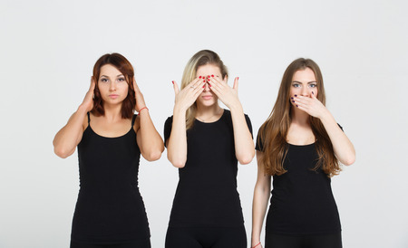 Three young woman in black clothes isolated at white background showing blind, deaf and dumb: wise monkey scene - hear no evil, see no evil, speak no evil Stock Photo