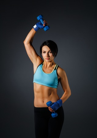 Young sportive strong brunette woman in sportswear studio shot makes fitness with dumbbells at grey background