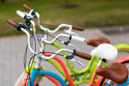 handlebars: Closeup of the three womans bright colored bicycles handlebars with hand break hook and leather saddles Stock Photo