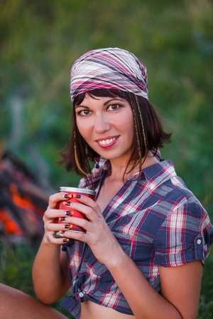 travel mug: Travel and camping - portrait of young slim sportive woman tourist brunette at the beautiful nature landscape sitting by the fire with drink in mug in her hands