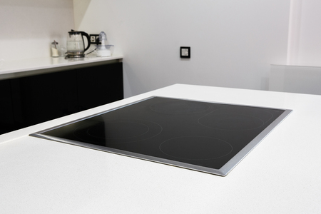 cooktop: Modern black induction stove, cooker, hob or built in cooktop with ceramic top in white kitchen interior